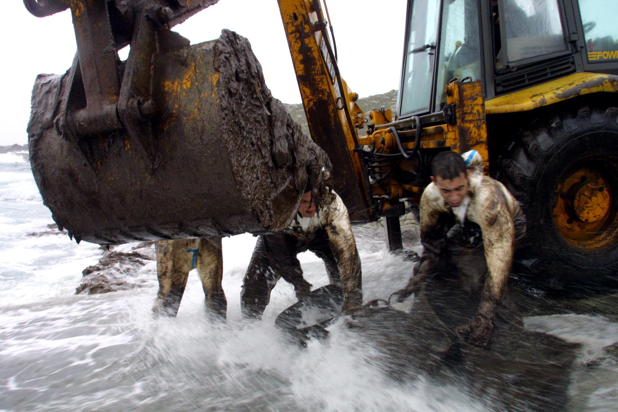 Una pala ayuda a las labores de limpieza en Touriñán (Muxía), en medio del fuerte oleaje. <br><b>José Manuel Casal</b>
