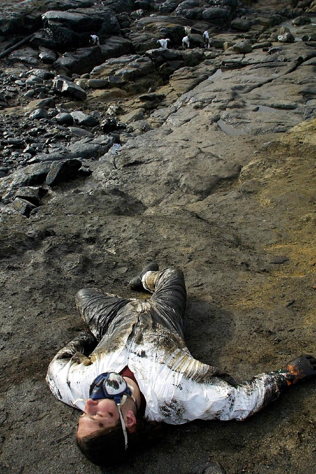 Un voluntario descansa en la playa de A Pedriña, en Muxía, después de trabajar durante toda una mañana. <br>Ana García