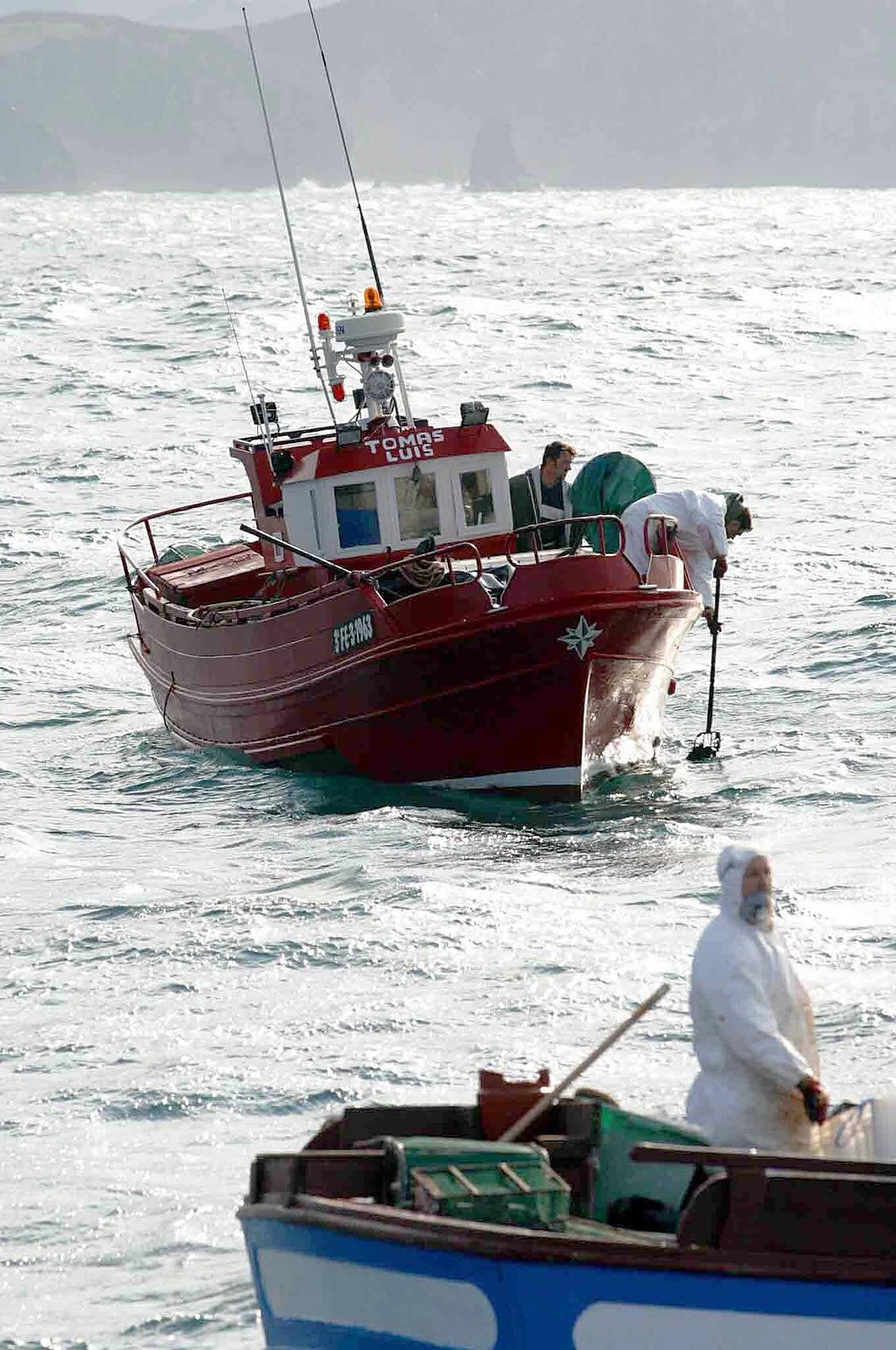 07/02/03 <br>Los marineros recogen galletas que aparecen flotando cerca de la costa de Cedeira <br>José Pardo