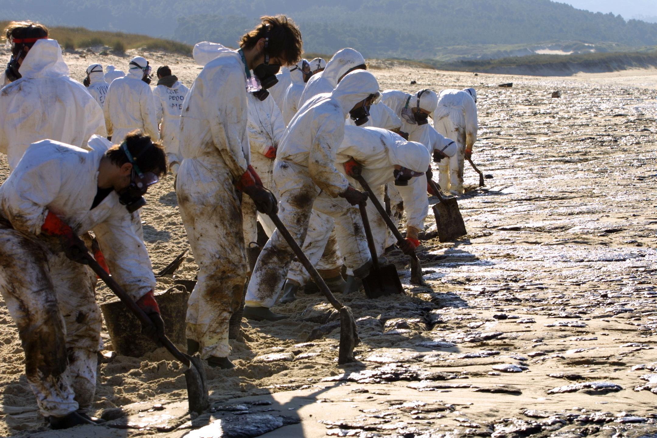 07/12/2002 <br>Voluntarios tratan de arrancar el fuel en la playa de O Rostro, en Fisterra  <br>José Manuel Casal