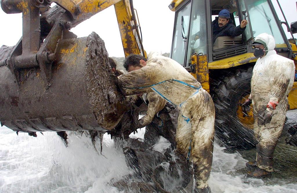 21/12/2002 <br>Percebeiros y voluntarios recurren a una excavadora para limpiar el fuel que el oleaje deposita en el puerto de Touriñán  <br>José Manuel Casal