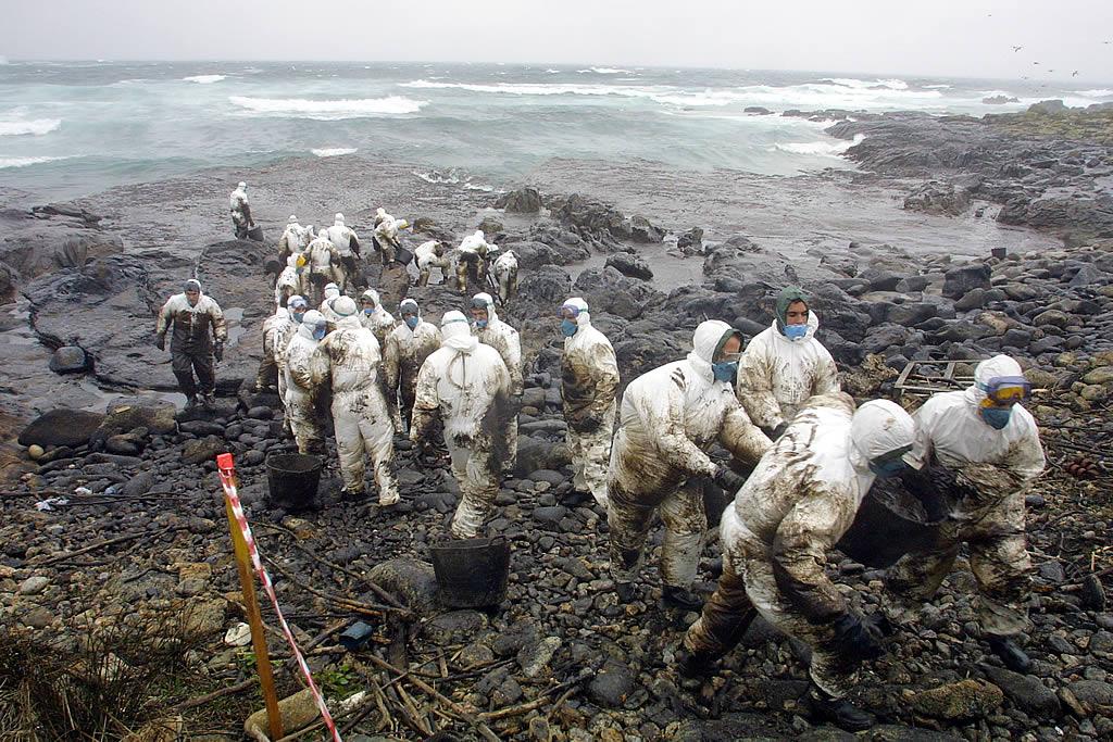 22/12/2002 <br /> Cadena humana de voluntarios subiendo capazos de chapapote en la playa de Lira <br />Álvaro Ballesteros
