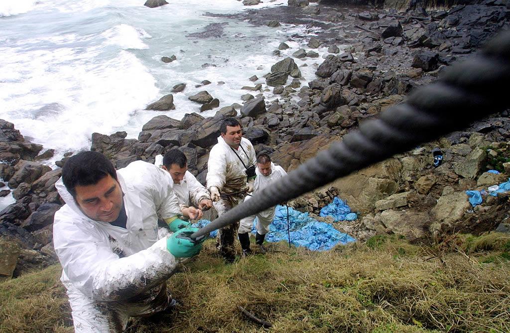 12/02/2003 <br>Un grupo de percebeiros abandonan la playa tras estar recogiendo fuel en una difícil zona entre O Rostro y Lires, en Fisterra <br>José Manuel Casal