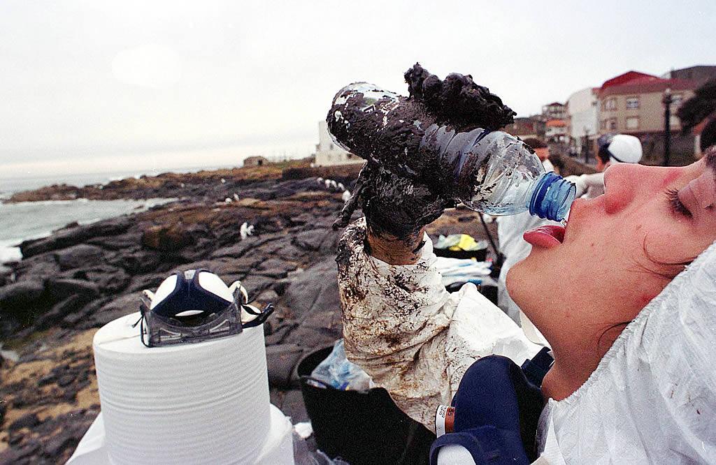 12/12/2002 <br> Un voluntario bebe agua en el paseo de Muxía <br>Álvaro Ballesteros