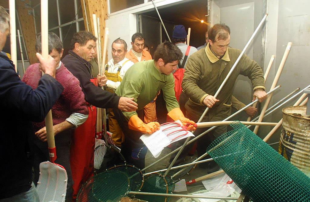4/12/2002 <br>Marineros de la cofradía de Bueu recogiendo rastrillos, horquillas y palas recubiertas con red de plástico para salir a recoger el fuel que ya estaba entrando en la ría de Pontevedra <br>Xoán Carlos Gil