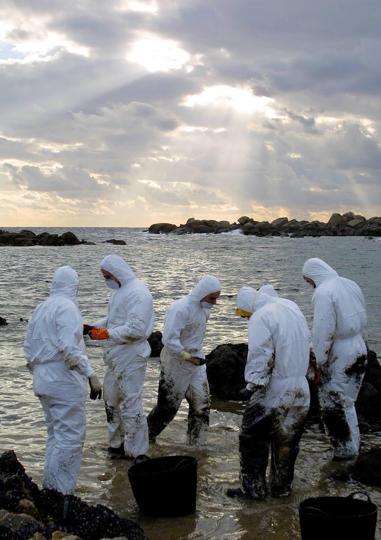 05/12/2002 <br>Los voluntarios comienzan a llegar a las playas de San Vicente de O Grove. Uniformizados por el mono blanco parecen tropezar aturdidos por la ingente marea negra <br>Vítor Mejuto