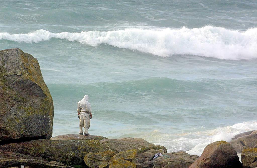 14/12/2002 <br>Playa de A Lanzada. Un voluntario observa impotente el mar esperando que deje de escupir fuel