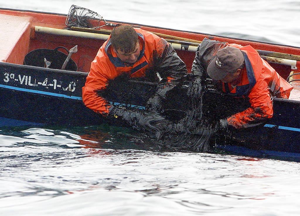 Retirada del fuel con las manos por parte de los marineros <br>Vítor Mejuto