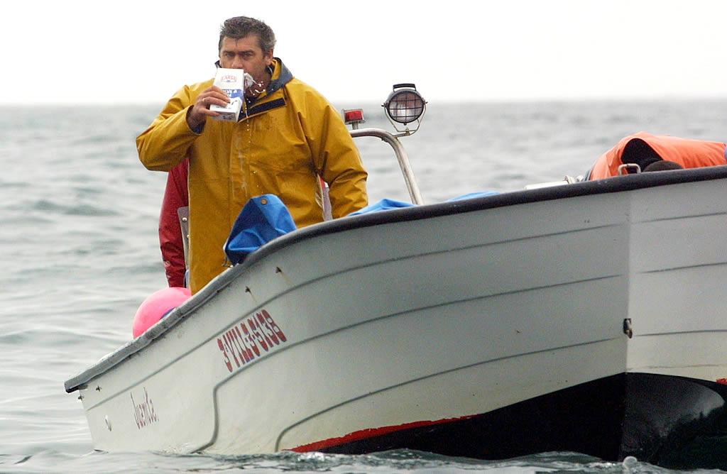 Desde un bote, voluntarios se dedicaron a repartir leche para minimizar los efectos nocivos del fuel <br>Vítor Mejuto