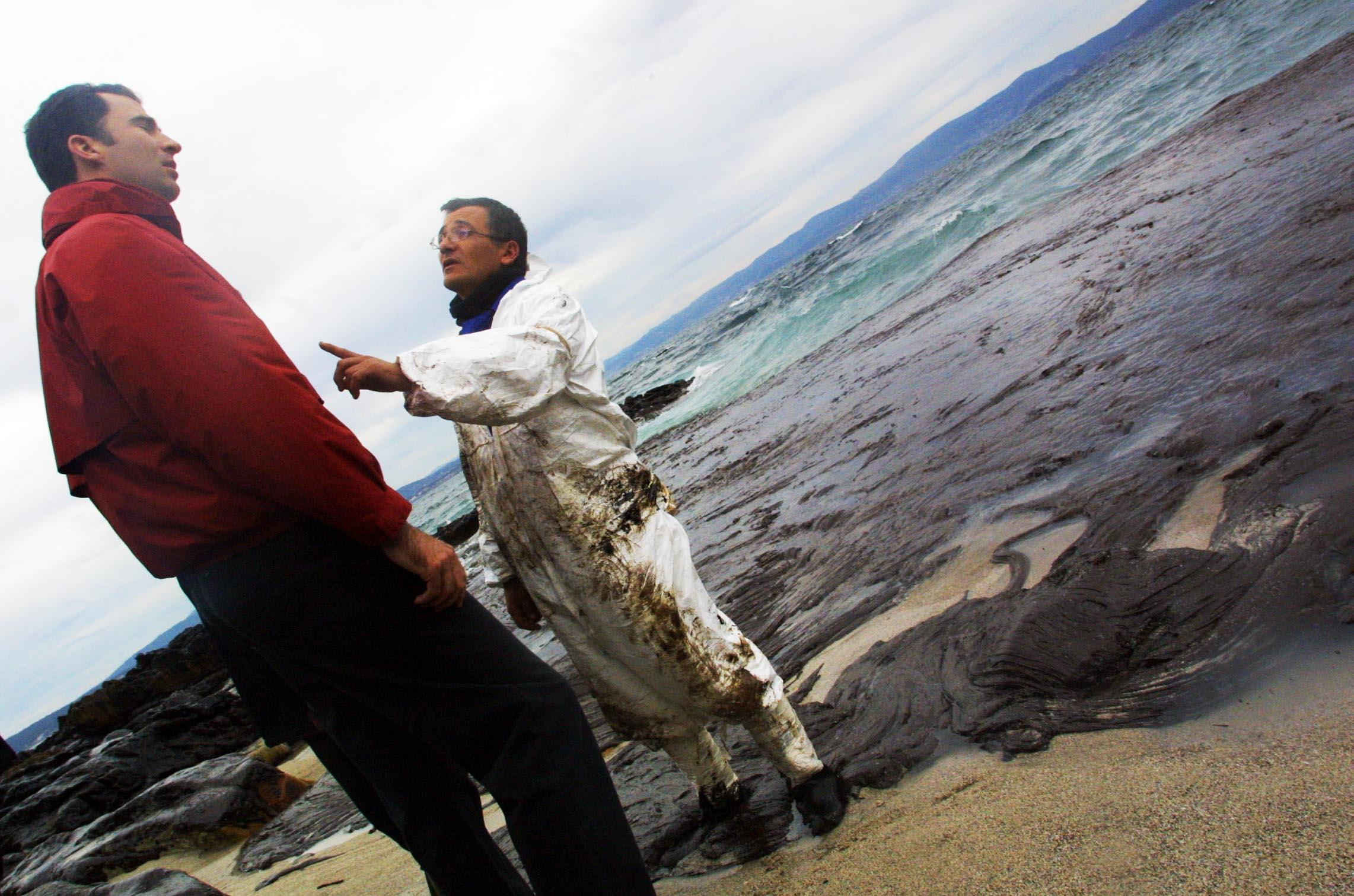 Un voluntario señala al Príncipe ante una playa atestada de chapapote. <br><b>Vítor Mejuto</b>