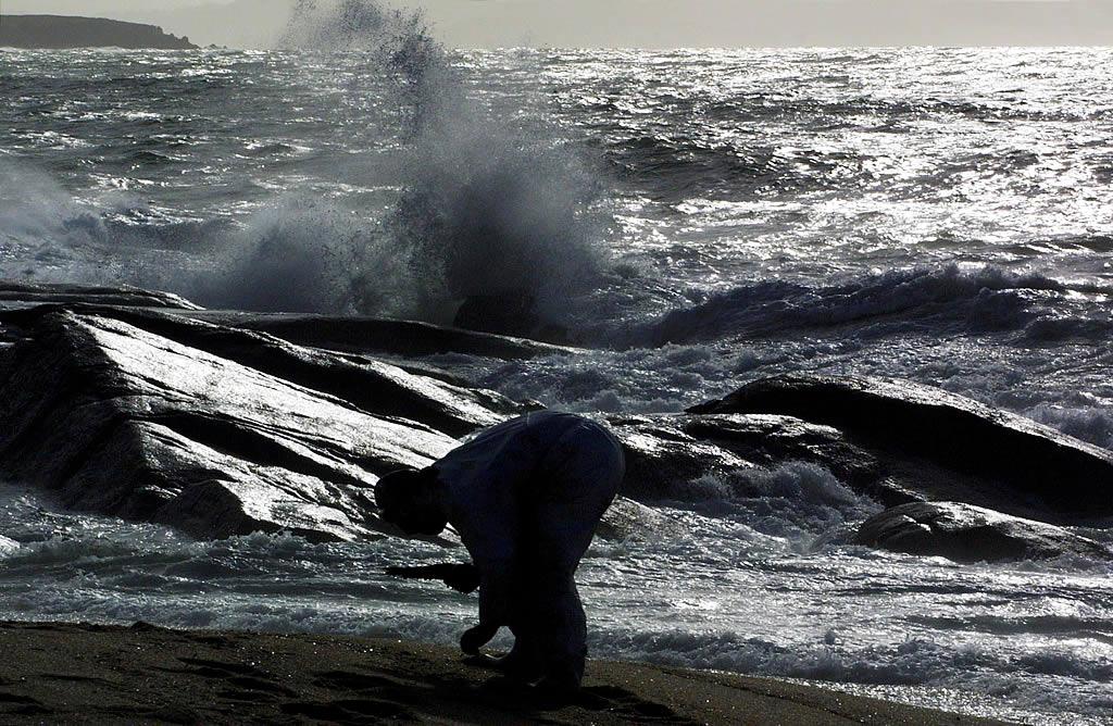Un voluntario recoge fuel en una playa de Arousa <br>Vítor Mejuto