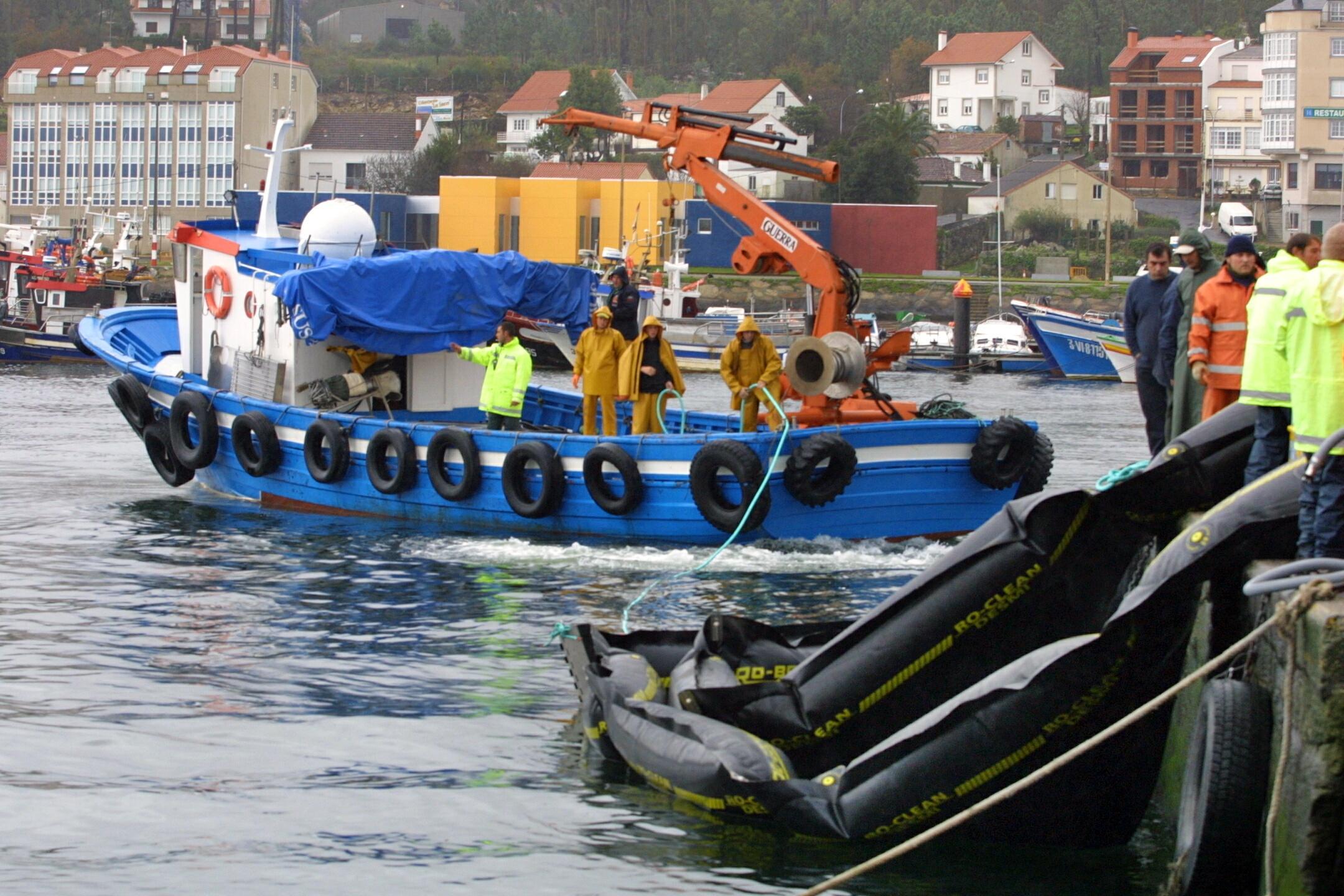 Un barco zarpa de Portosín para colocar las barreras.<br><b>Carmela Queijeiro</b>