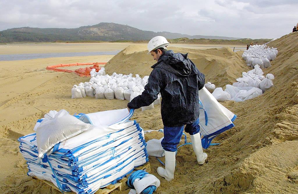 Un operario coloca sacos de arena para proteger el parque natural de Corrubedo<br><b>Carmela Queijeiro</b>