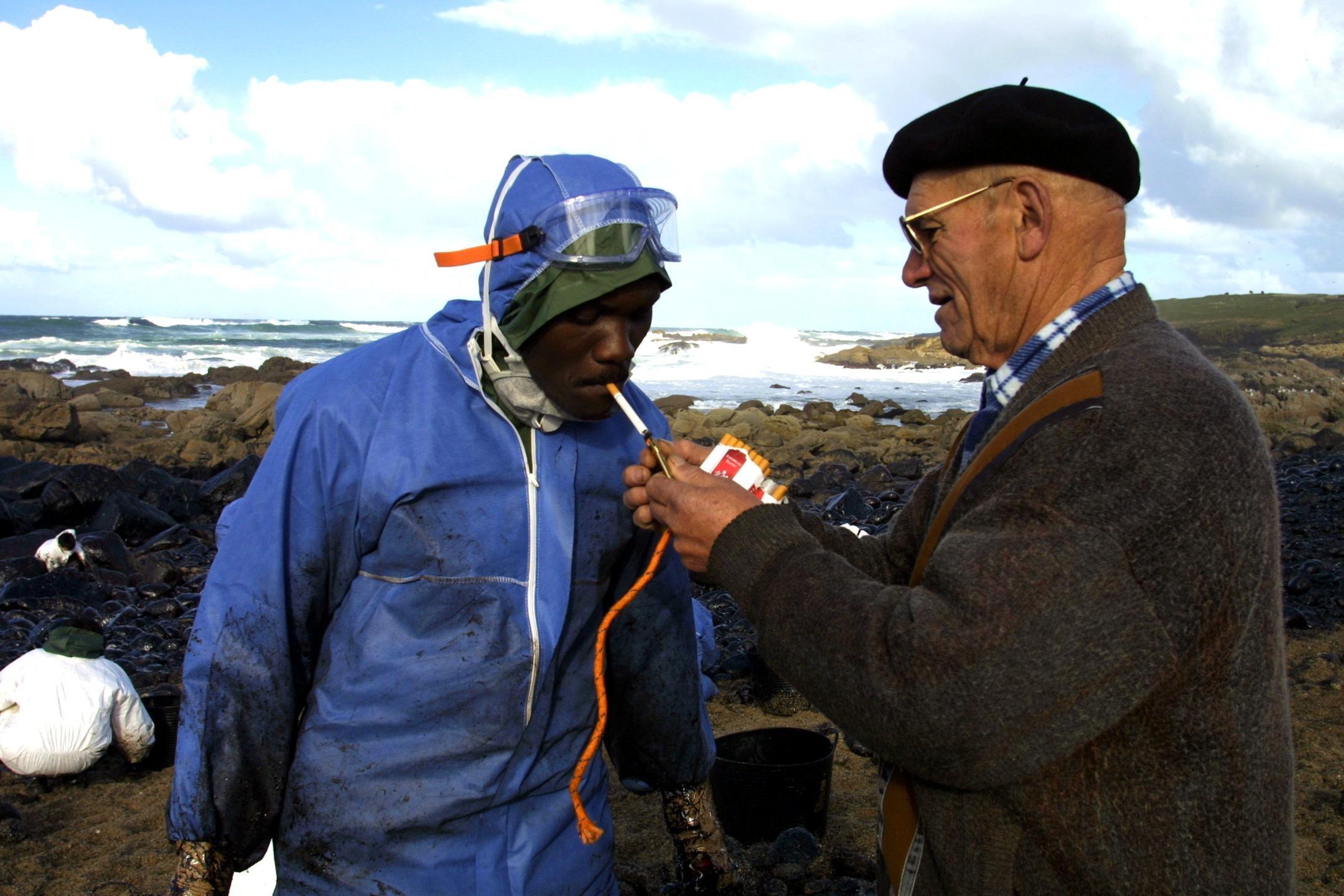 Un muxián que reparte tabaco entre los voluntarios le ofrece fuego a un joven <br><b>José Manuel Casal</b>