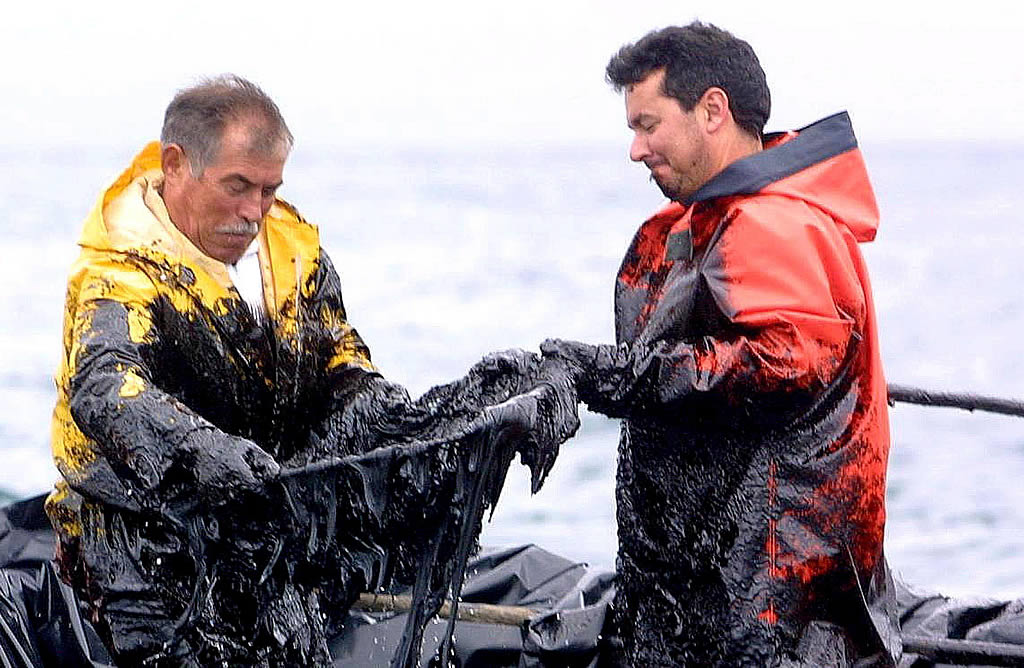 Dos marineros retiran fuel. <br> Vítor Mejuto