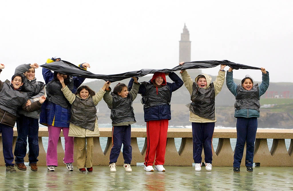 Un grupo de niños salta con la Torre de Hércules al fondo.  <br><b>César Quián</b>