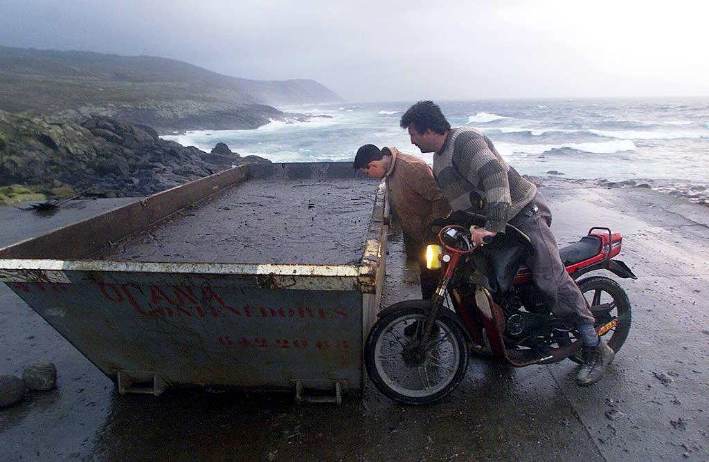 18/12/2002 <br /> Vecinos bajan a la playa al anochecer a ver contenedores de chapapote en la cala Touriñán <br />Álvaro Ballesteros