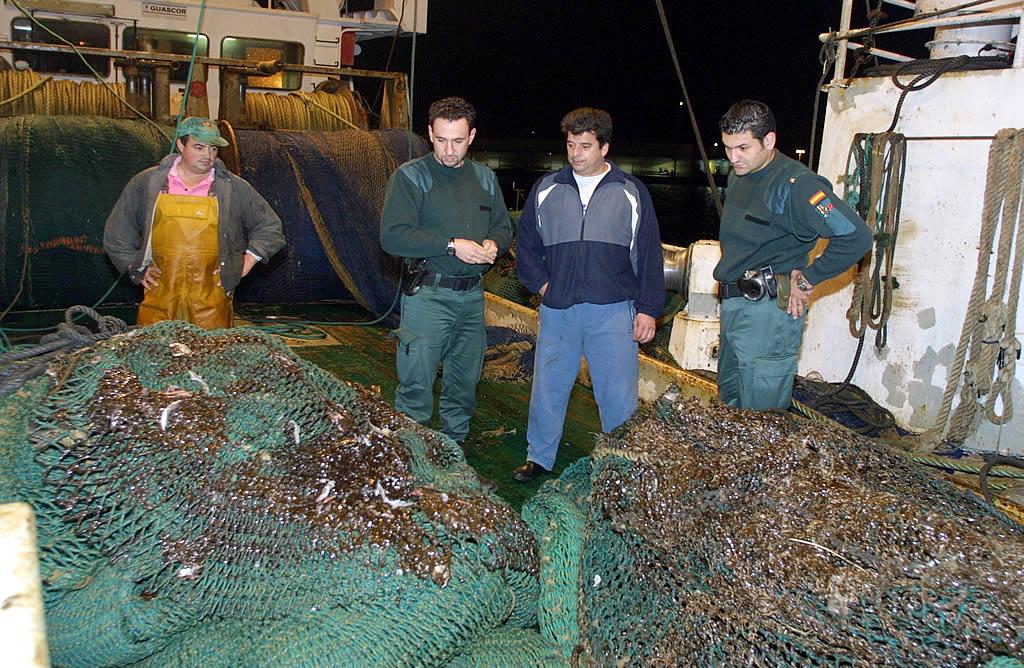 Un marinero y dos guardias civiles contemplan las redes manchadas de fuel de un arrastrero en Celeiro. <br><b>Xaime Ramallal</b>
