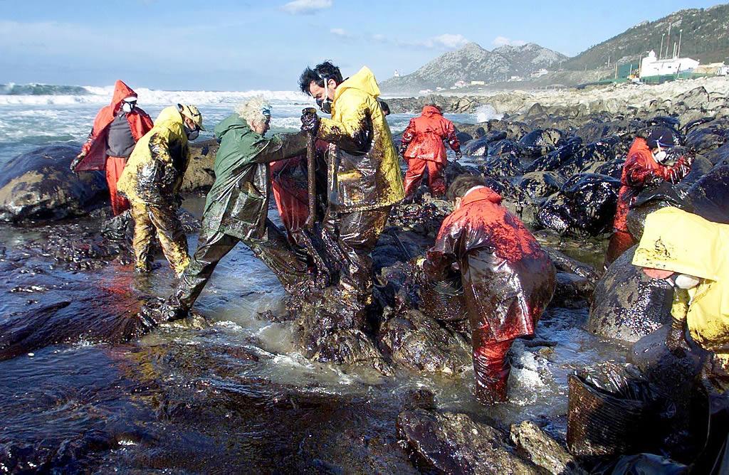 05/12/2002 <br> Los voluntarios limpian el fuel en la costa de Mougás, en Santa María de Oia <br>Óscar Vázquez