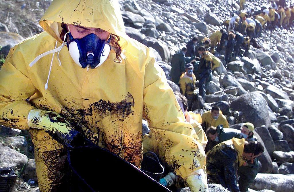 07/12/2002 <br>Los voluntarios se afanan en arrancar el chapapote de la rocas en Mougás, Oia <br>Óscar Vázquez