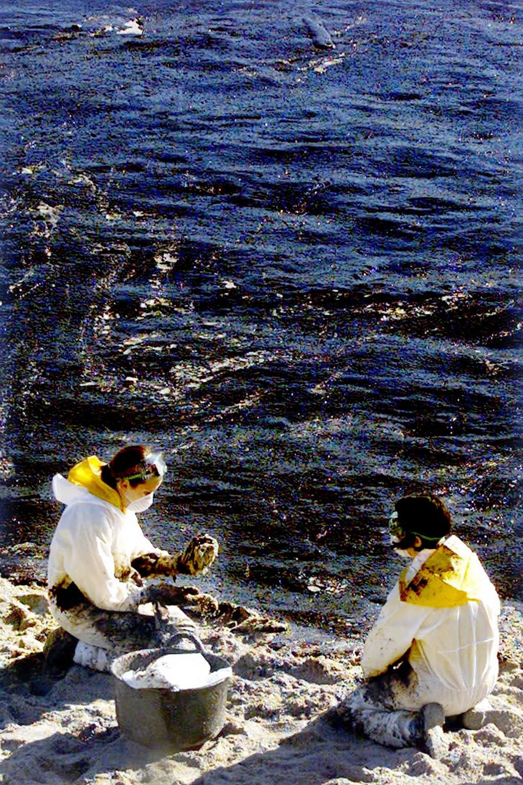 10/12/2002 <br> Dos volutarios limpian el fuel que llegó a las costas de Ons <br>Óscar Vázquez