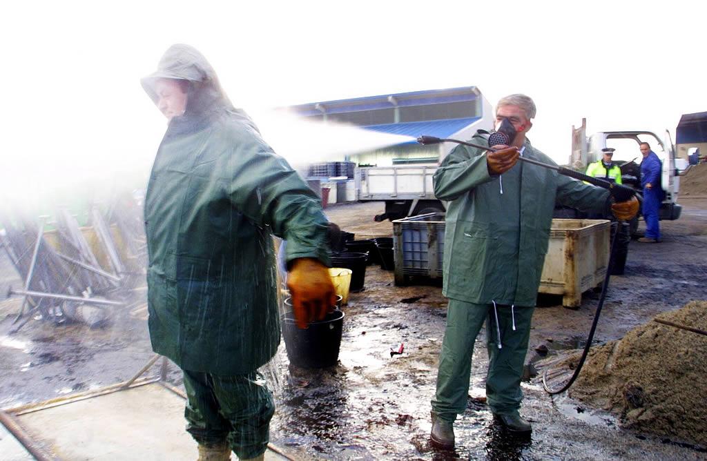 12/12/2002 <br> Tras una jornada recogiendo fuel, los voluntarios limpian sus trajes con agua a presión <br>Óscar Vázquez